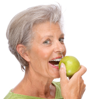 Senior woman eating an apple